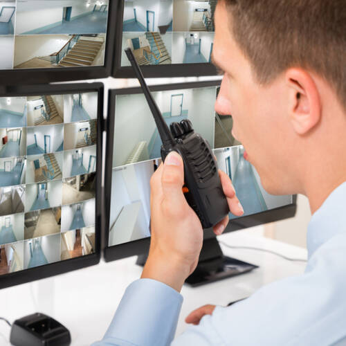 Close-up Of Male Security Guard Talking On Walkie-talkie While Monitoring Multiple CCTV Footage